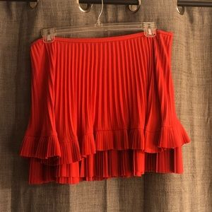 Coral pleated mini skirt with ruffle detail